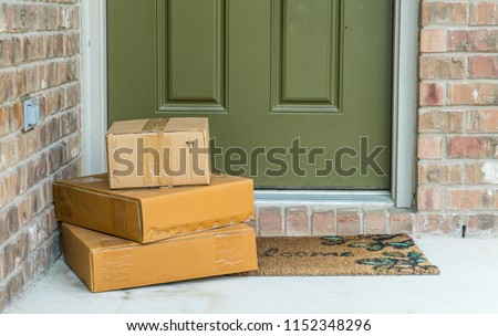 Package delivery on doorstep. Boxes and postal delivery on modern brick home doorstep on front porch #1152348296
