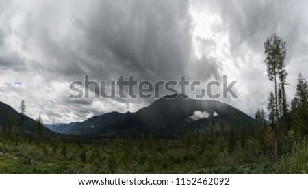 Sun rays peak through a rainstorm in a valley in the Canadian wilderness #1152462092