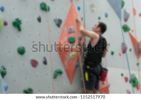 Blurred background of Rock Climbing Simulation Indoor and man climbing up the climbing wall. #1152517970