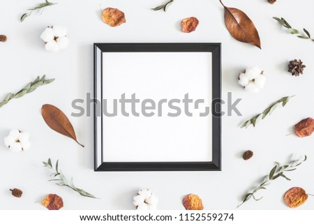 Autumn composition. Photo frame, dried flowers and leaves on pastel gray background. Autumn, fall concept. Flat lay, top view, copy space