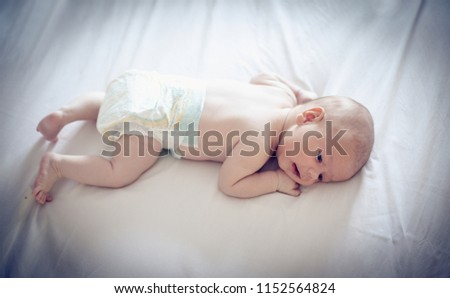 Little baby boy in diaper lying on bed. Close up. Space for copy. #1152564824