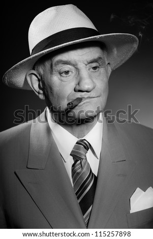 Senior glamour vintage man wearing suit and tie and hat. Black and white studio shot. Gangster look. Smoking cigar and drinking glass of whisky. Isolated.