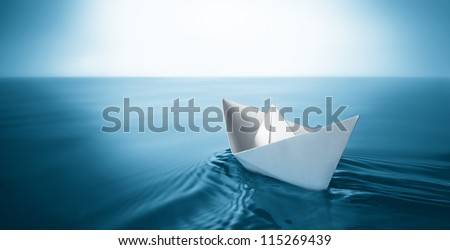 origami paper sailboat sailing on blue water #115269439