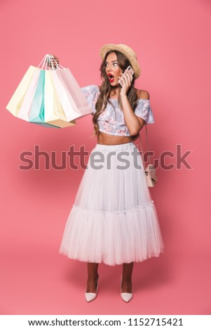 Full length portrait of excited woman wearing straw hat and fluffy skirt holding colorful paper shopping bags and talking on mobile phone isolated over pink background #1152715421