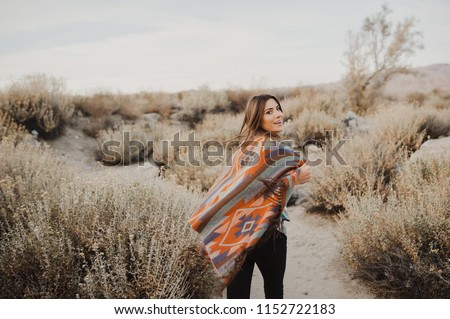 Smiling, beautiful hipster traveler girl in gypsy look and windy hair, in desert nature.  Artistic photo of young hipster traveler girl in gypsy look, in Coachella Valley  #1152722183
