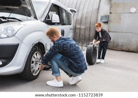 father changing tire in car with wheel wrench, son holding tire #1152723839