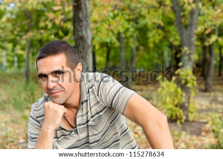 Attracive middle-aged thoughtful man sitting with his chin on his fist giving the camera a slight smile with a woodland backdrop and copyspace #115278634