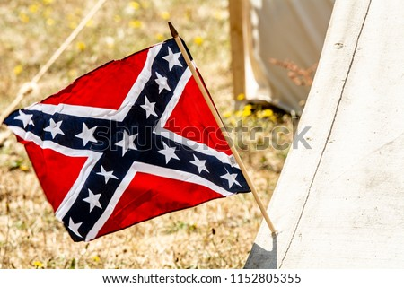 Confederate flag on the side of a canvas tent suggesting a civil war confederate camp #1152805355