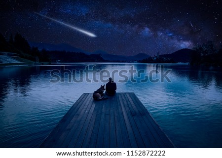 Man with dog looking at Perseid Meteor Shower at lake Bled #1152872222