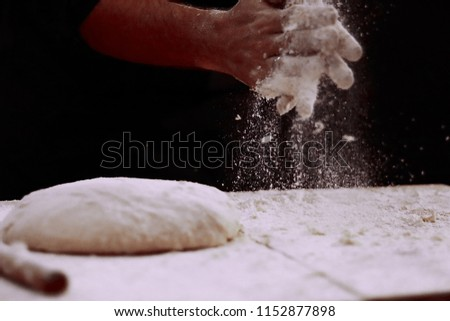 Man baking bread. Sprinkling some flour on dough. Hands kneading dough.  Male chef prepares a meal of flour.  #1152877898