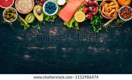 A set of healthy food. Fish, nuts, protein, berries, vegetables and fruits. On a black wooden background. Top view. Free space for text. #1152986474