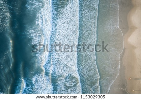 Aerial view of a beach with breaking waves Royalty-Free Stock Photo #1153029305
