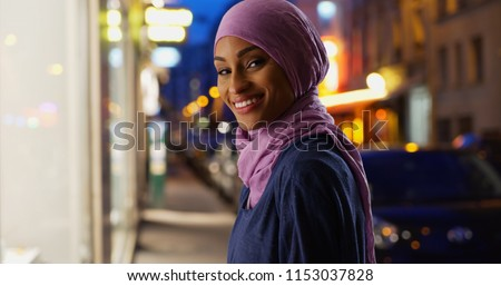 Beautiful young Muslim woman in urban setting smiling at camera Royalty-Free Stock Photo #1153037828