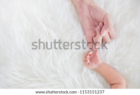 Asian parent hands holding newborn baby fingers, Closeup mother's hand holding their new born baby. Together love harmony peace family nursery healthcare and medical father's day concept banner #1153151237