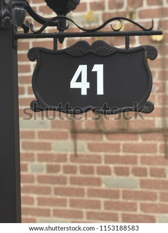 House sign number 41 on black background hanging from post outside red brick background