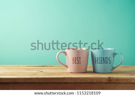 Coffee cups on wooden table. Friendship day celebration background
