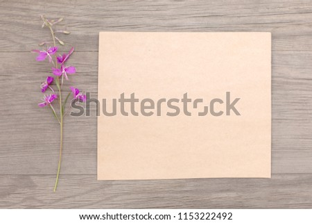 Blooming sally purple flowers with craft paper blank on old grunge wooden background. Top view. Minimalistic mockup. #1153222492