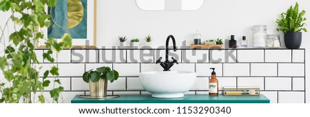 Green cabinet with fresh plant, bottle with soap and white sink with black tap in real photo of bright bathroom interior #1153290340