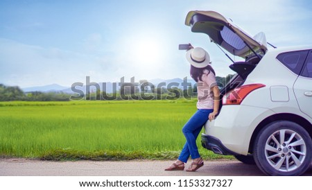 Car parking on Countryside road and young Woman traveler sitting on hatchback car taking selfie picture against blue sky background and green grass field. Woman travel alone in holiday concept.