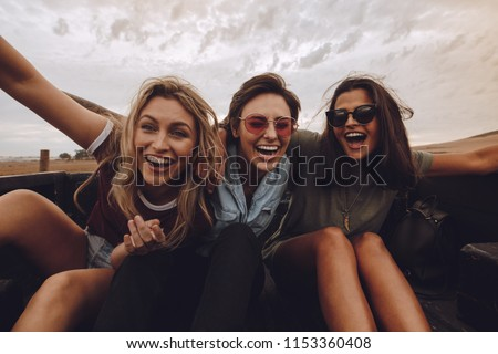 Portrait of three women sitting on back of a pickup truck and laughing. Female friends enjoying a pick truck ride in countryside road trip. #1153360408