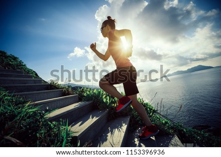 Woman runner running up on seaside mountain stairs #1153396936