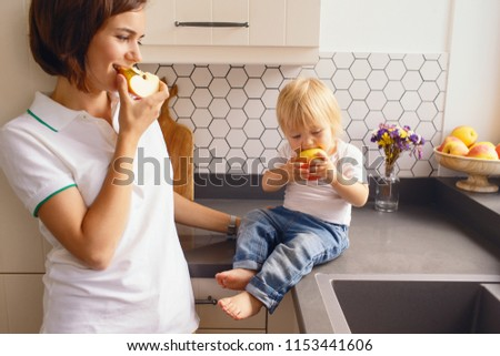 Mother cooking at home with child. Having fun in kitchen. Parenting concept #1153441606