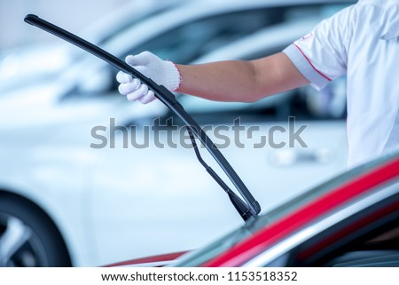 Technician is changing windscreen wipers on a car station. Royalty-Free Stock Photo #1153518352
