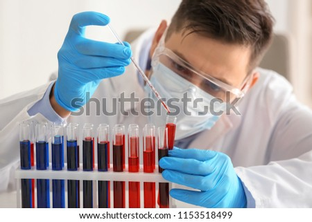 Scientist working with test tubes in laboratory #1153518499