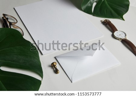 Business mock up set with envelope and watch on white marble background with monstera leaves #1153573777