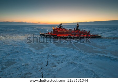 Icebreaking vessel in Arctic with background of sunset Royalty-Free Stock Photo #1153631344
