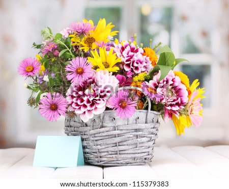 beautiful bouquet of bright flowers in basket on wooden table #115379383