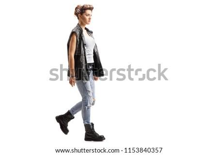 Full length profile shot of a punk girl walking isolated on white background #1153840357
