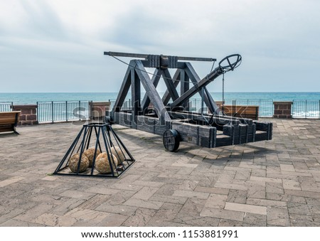 ancient catapult on the ramparts of Alghero ,Sardinia Island, Italy , Defensive wall. Catapult in the downtown of the citywith the sea as background and the big stone bullets in front #1153881991