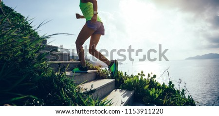 Determined woman running up on seaside mountain stairs  #1153911220