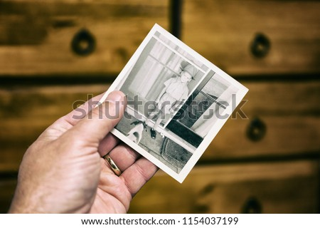 A person looking at an old photograph of a  child's first day at school.