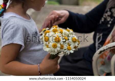 celebrate the victim feast of the elders on the religious holidays.happy mother and teachers day.kiss the mum hand.woman and kid hold the daisy.