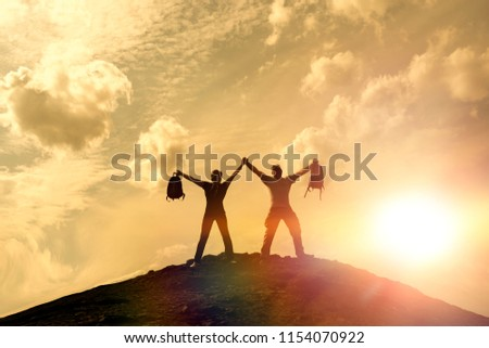 silhouettes of happy men and girls on top of a mountain. against the background of sunset.  #1154070922