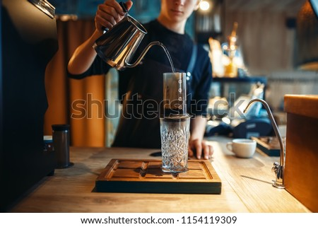 Barista pours water from coffee pot into the glass #1154119309