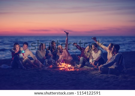a group of friends using cell phones around the bonfire during autumn beach party drinking beer and having fun #1154122591