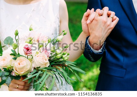 Husband and wife in blue suit and wedding dress getting married and holding hands #1154136835