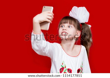 Little girl with crazy face hold telephone and take picture on red background. Communication concept