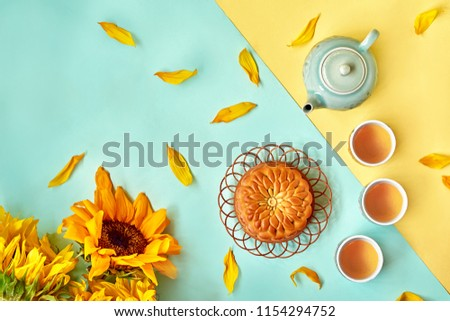 Chinese Mid Autumn Festival Moon cake and tea on color background Royalty-Free Stock Photo #1154294752