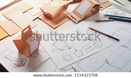 Designer sketching drawing design Brown craft cardboard paper product eco packaging mockup box development template package branding Label . designer studio concept . #1154323708