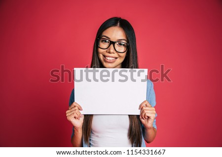 Beautiful young cute lovely asian woman in glasses with white blank board or banner in hands for advertisement over pink background #1154331667
