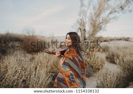 Happy, beautiful hipster traveler girl in gypsy look and windy hair, in desert nature.  Artistic photo of young hipster traveler girl in gypsy look, in Coachella Valley in a desert valley in Souther #1154338132