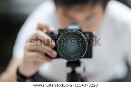 The photographer taking a photo with his camera on tripod,front view with shallow DOF. #1154373220