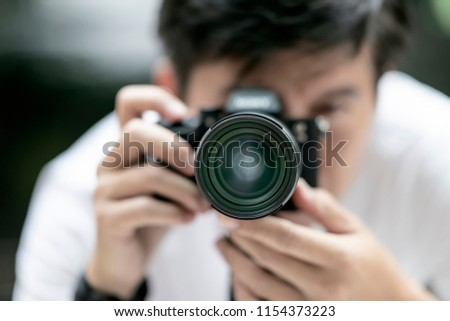 Close up view of  photographer taking a photo with his camera on tripod,front view with shallow DOF. #1154373223