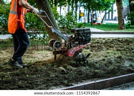 group of workers in the street cultivating soil with traktor machine to plant some trees in the city #1154392867