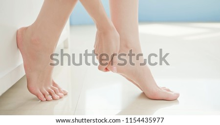 beauty woman apply cream with foot at home Royalty-Free Stock Photo #1154435977