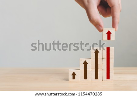 Hand arranging wood block stacking as step stair with arrow up. Ladder career path concept for business growth success process #1154470285